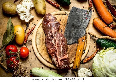 Beef with a meat axe and ingredients for soup. On a wooden table.