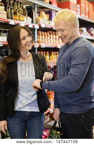 Happy Customers Using Smart Watch In Grocery Store