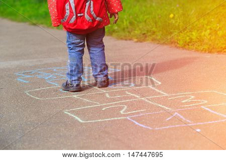 little girl playing hopscotch game after school, kids outdoor activities