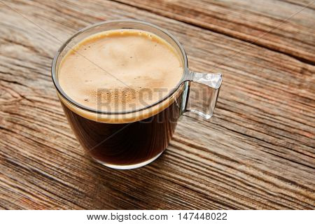 Coffee glass cup with cream on wooden table