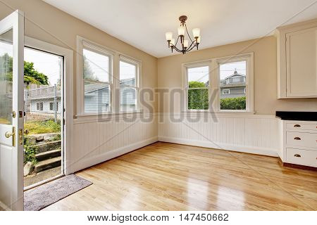 Empty Hallway Interior With Hardwood Floor And Opened Door To Backyard