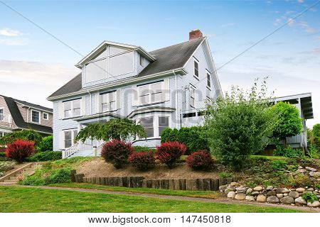 Traditional Three Story House Exterior With Well Kept Garden Around.