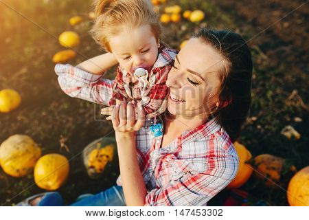 mother playing with her daughter on a field with pumpkins, Halloween eve