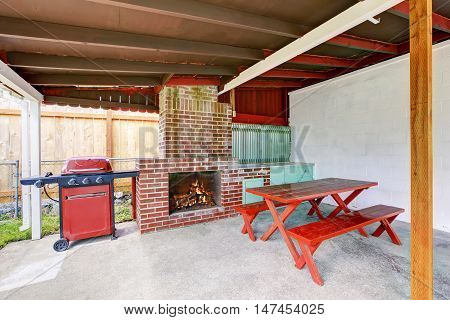 Exterior Covered Patio With Brick Fireplace And Furniture.
