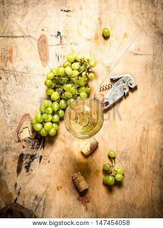 glass of white wine with grapes and a corkscrew. On wooden background.