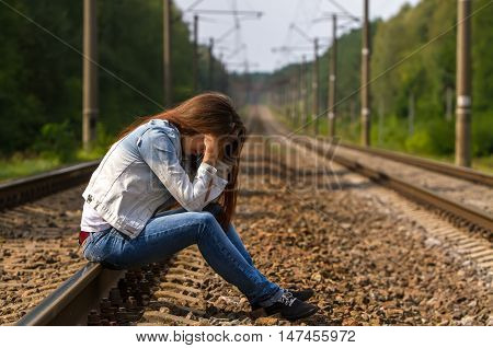 The girl in denim suit sits on rails desperately bent head supports her hands.
