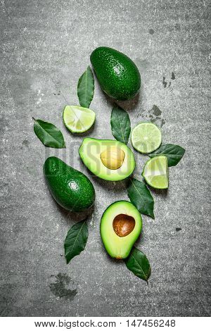 Avocado and lime . On a stone background.