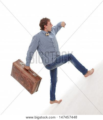 young man with a suitcase in a hurry. guy looks at his watch and walks up the hill. business concept. isolated on white background