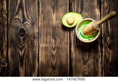 The guacamole in a mortar with pestle. On wooden background.