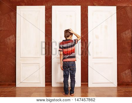 concept of choice. doubting boy stands in front of three closed doors. view from the back