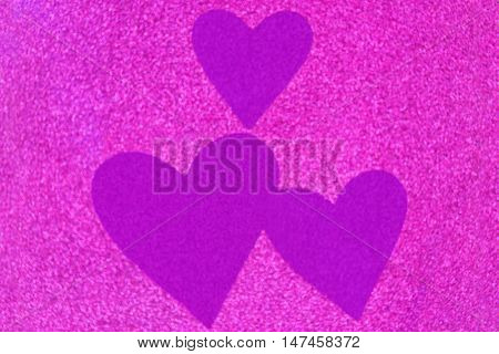 Glittery texture of glitter in magenta with blurred purple violet heart. Abstract background photo