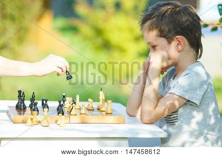 boy pondering chess game. kid playing chess with an adult outdoors. the concept of education