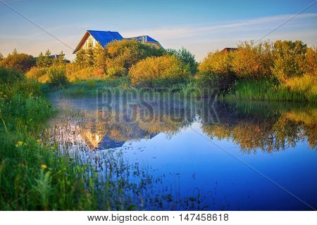 autumn rural landscape. houses, pond and bushes in the light of the setting sun