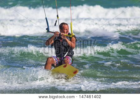 Athletic Man Riding On Kite Surf Board In Sea Waves