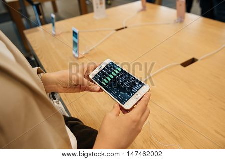 PARIS FRANCE - SEPTEMBER 16 2016: New Apple iPhone 7 Plus being tested by woman after purchase - . New Apple iPhone tends to become one of the most popular smart phones in the world in 2016