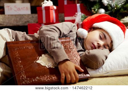 Cute little boy falling asleep with book while waiting to catch Santa Claus