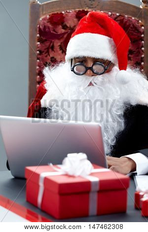 A portrait of Santa Claus in formalwear sitting in an armchair and typing on a laptop