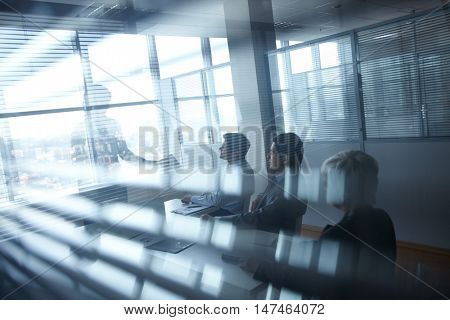 Business meeting of four people in black-out office room
