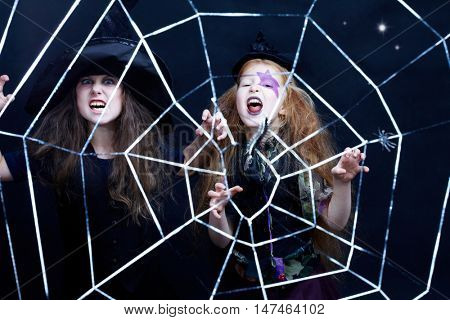 Two girls dressed in witches looking at camera and grimacing behind the cobweb against black background