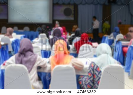 Blur blurred focus  of university students. sitting in a lecture room with a teacher in front of the class with white projector slide screen : view from the back of the classroom: