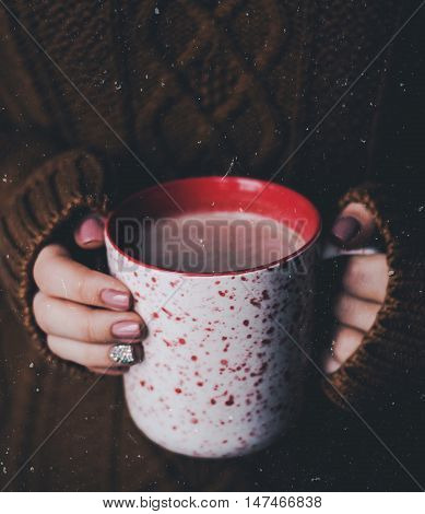Cozy atmosphere, a cup with coffee or cacao in the hands