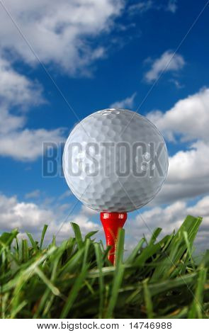 Golf ball and tee over a blue sky and clouds.