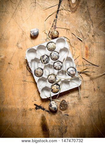Quail eggs in a cassette. On wooden background.