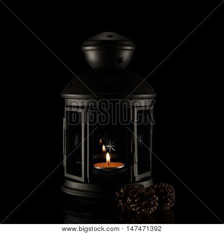 Candlestick with burning candle on a black background.