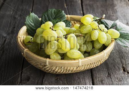 Clusters Of Green Grapes In Wattled Bowl On A Dark Wooden Background