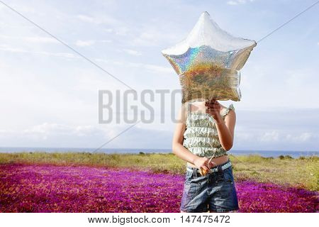Front view of preadolescent girl holding star shaped balloon in front of her face while standing at flower field