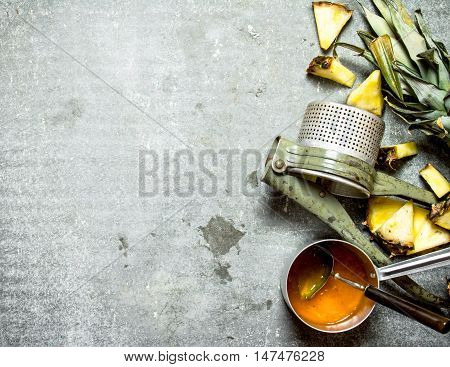 Pineapple jam with a manual juicer. On a stone background