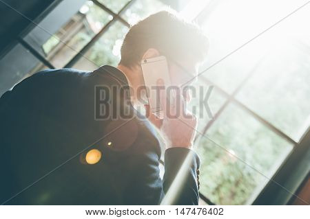 Staying in touch with colleagues. Low angle rear view of confident young man talking on the mobile phone and looking away while standing in front of the big window indoors