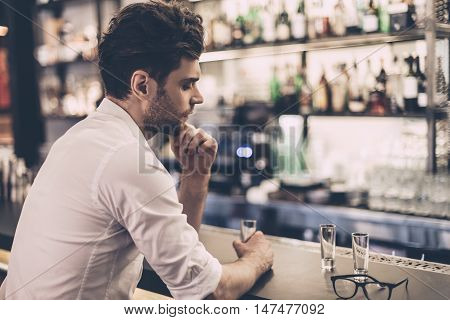 Feeling hopeless. Frustrated young man in shirt sitting at the bar counter and holding glass