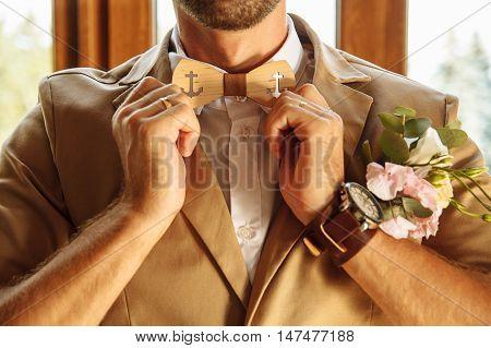 man straightens his tie wooden tie brown