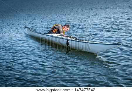 man rolling with a kayak on a lake - serial pictures 1 of 11