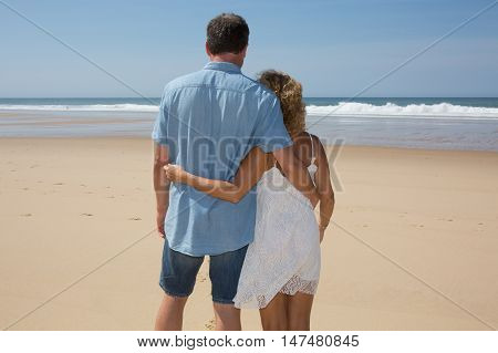 Vacation Couple Walking On Beach Together In Love Holding Around Each Other. Happy Interracial Young