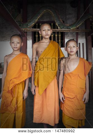LUANG PRABANG LAO PDR - August 2011: Three unidentified Buddhist novice monks residing at an old temple in Luang Prabang, Laos