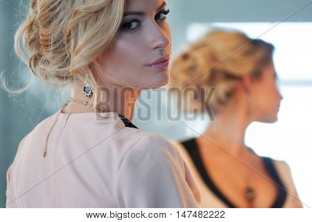 Fashion model with blond hair. Young attractive woman, stylish. Attractive woman in evening dress, the reflection in the mirror in the background