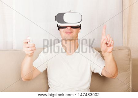 Happy handsome man wearing a virtual reality headset sitting on a sofa at home in livingroom.