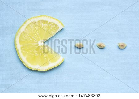 Creative concept photo of a lemon slice eating seeds on blue background.