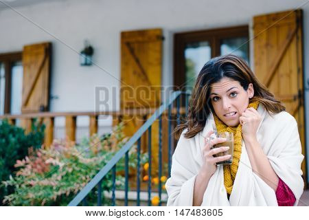 Woman Drinking Coffee Outside Home On Freezing Cold Autumn