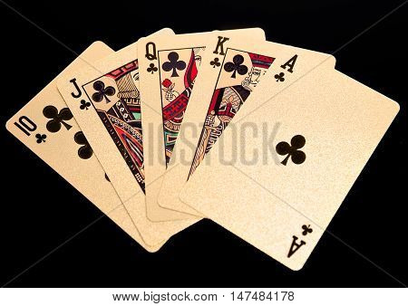 Royal straight flush golden playing cards poker hand. On black background