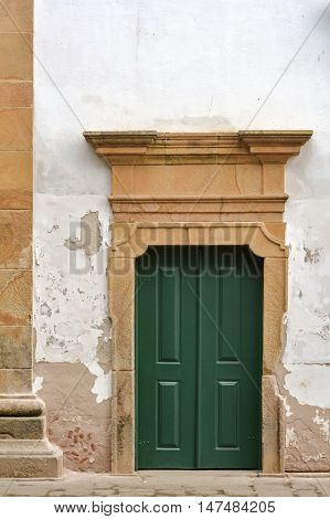 Old and aged wooden church door with stone frame in Paraty city Rio de Janeiro