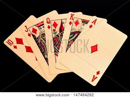 Royal straight flush playing golden cards poker hand in diamonds. On black background