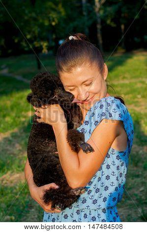 girl hugging a black poodle in nature summer day