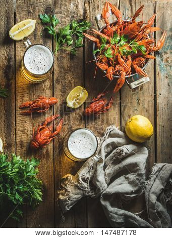 Two pints of wheat beer and boiled crayfish with lemon and parsley over old wooden rustic background, top view