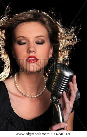 Beautiful woman singing into a vintage microphone