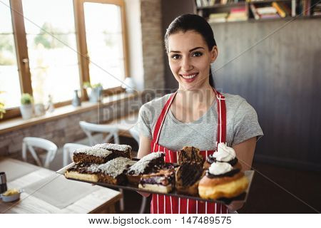 Portrait of female baker holding a tray of sweet foods in bakery shop