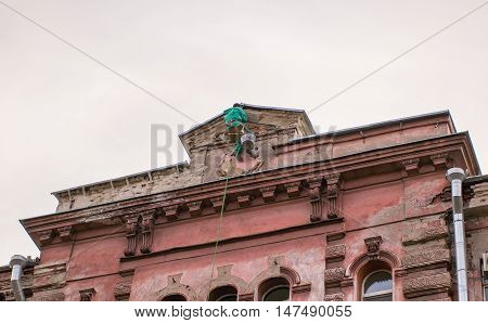 builder-climber hanging on the top of the facade of a building.