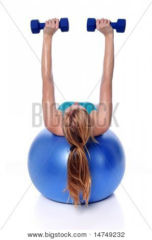 Young woman exercising with dumbbells laying on a fitness ball